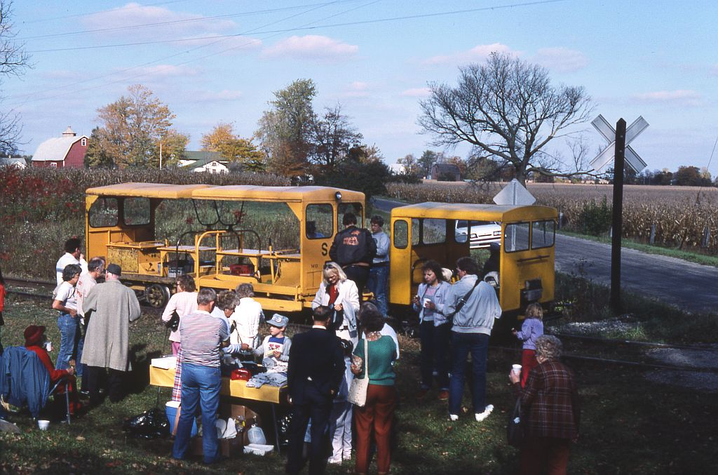 An SMRS fall color train lays over at Raisin Center, MI on 13 October 1985, the first year of the color tours. Passengers are sampling cider and donuts, while the crew prepares the motor cars for the return trip.