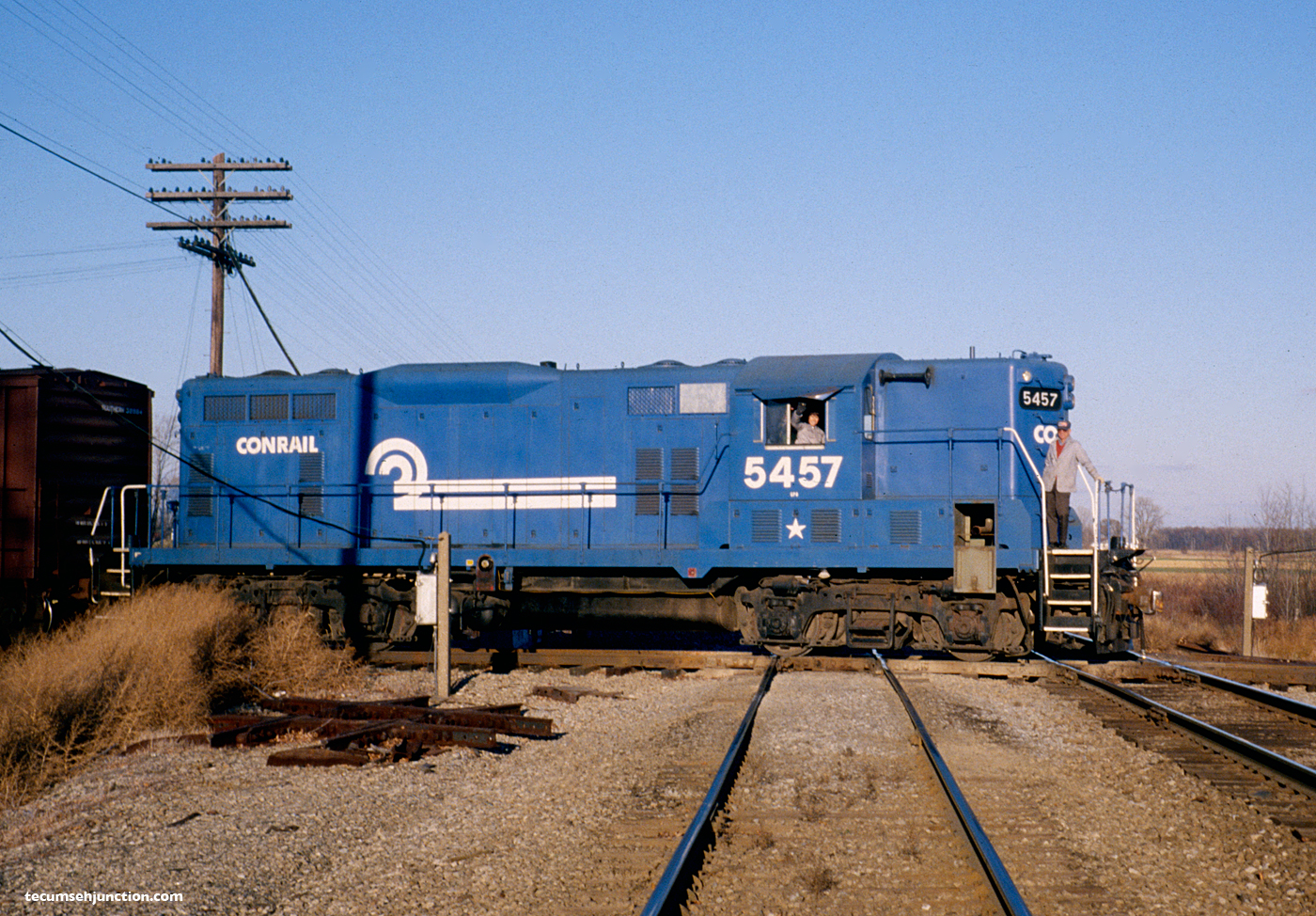 Conrail GP-8 #5457 leads the southbound CSR-1 over the Norfolk and Western Railway diamonds at Raisin Center, MI on 10 November 1980