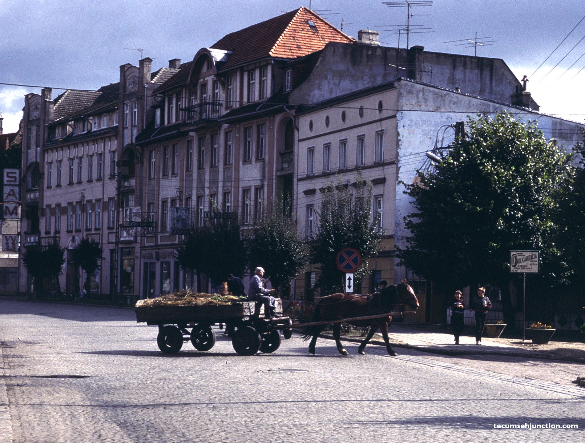 A horse-drawn cart turns off the main street in Czersk, Poland