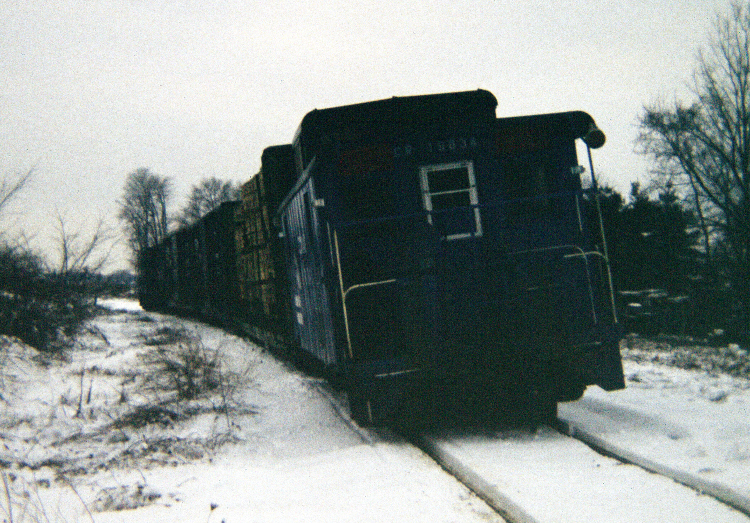 Conrail 19834 brings up the rear of the train at Lenawee Junction, Michigan. (12 December 1981)