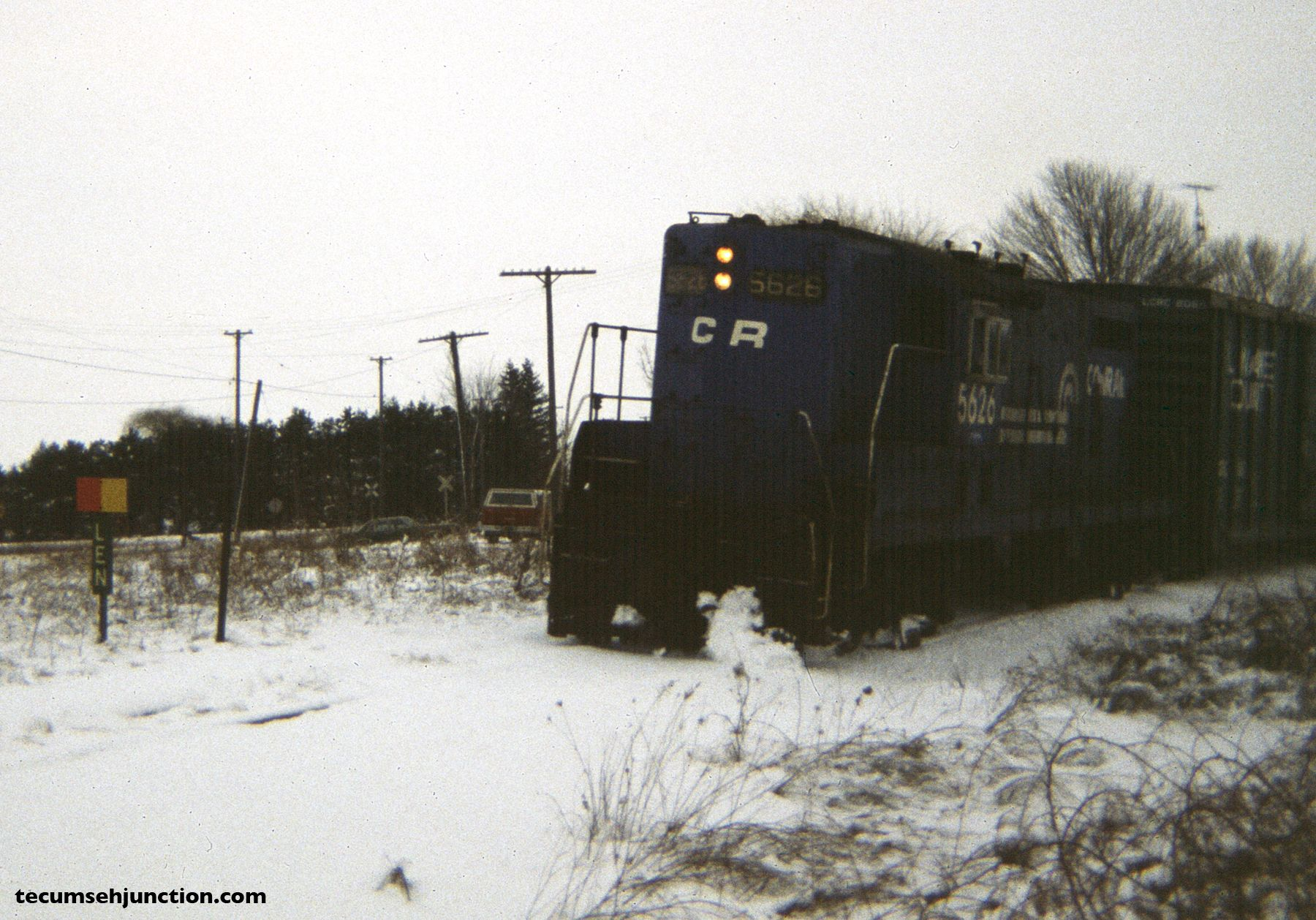 """Conrail 5626 rides the curve on the """"Old Road"""" side of the wye at Lenawee Junction, MI, to reach the Lenawee County Railroad interchange. (12 December 1981)"""