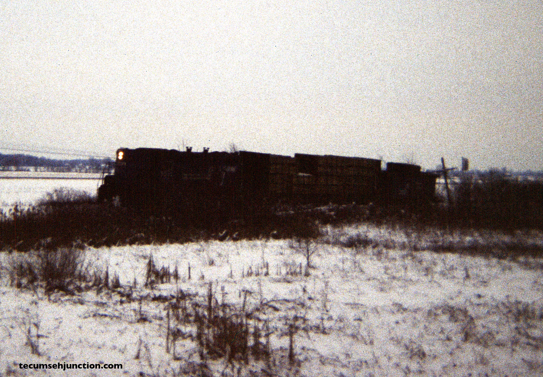 Having dropped off cars to the Lenawee County Railroad, the train heads north with just one car, here passing the approach signal to the N&W diamonds at Raisin Center, Michigan.. (12 December 1981)