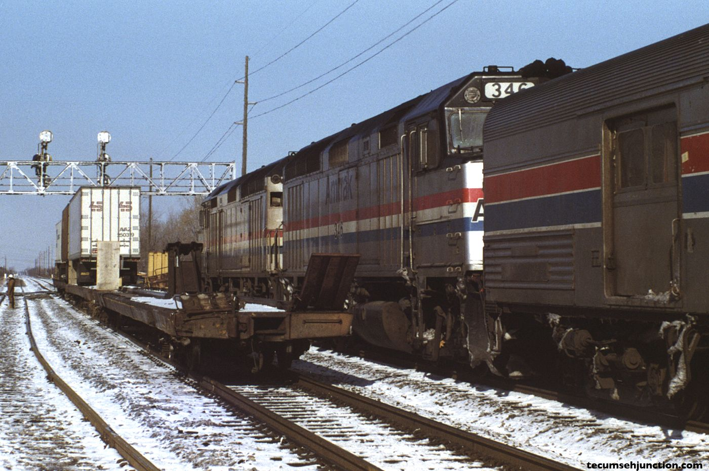 """Amtrak train #49, the westbound """"Lake Shore Limited"""", passes the wreck site. Cars from Mail-8 sit on the main line."""